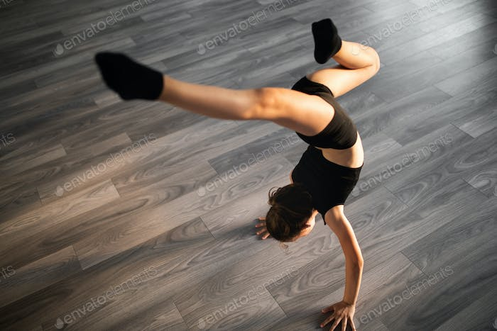 Beautiful girl practicing and exercising modern ballet at dance school