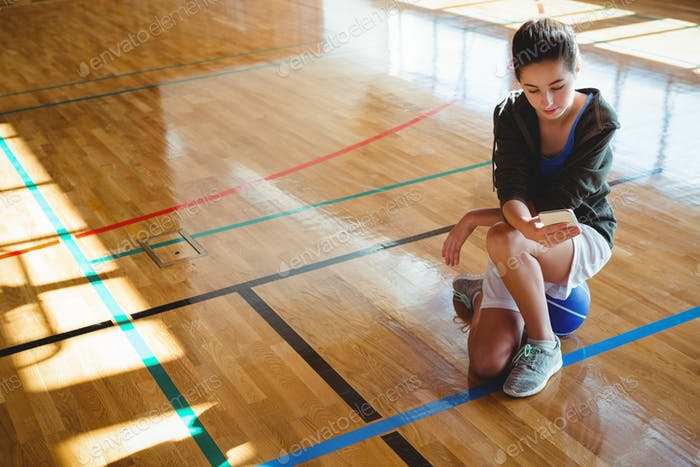 Female basketball player using mobile phone in court