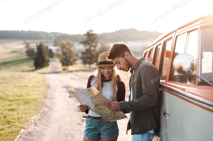 A young couple on a roadtrip through countryside, looking at a map.