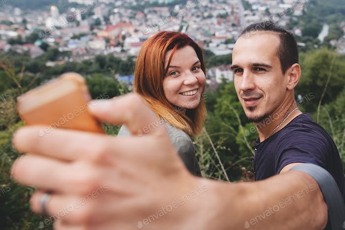 Happy hipster couple taking selfie on phone on background of beautiful view