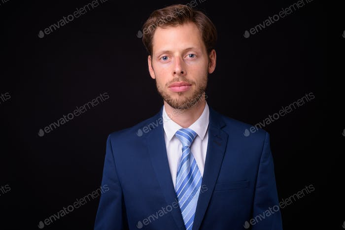 Face of bearded businessman in suit looking at camera