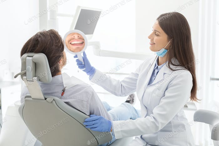 Pretty dentist showing her patient mirror to check treatment result
