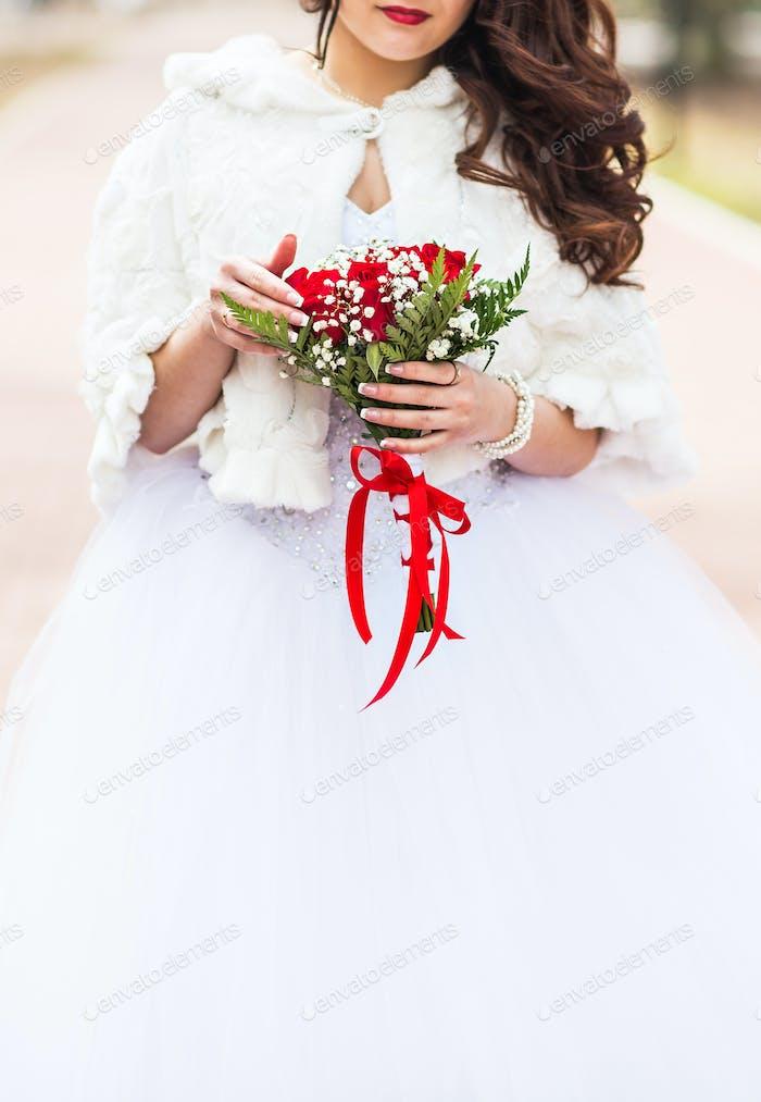 Braut mit dem Blumenstrauß im Winter