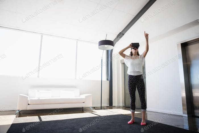 Full length of businesswoman using virtual reality simulator