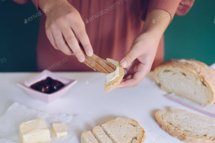 Frauen Hand verteilt Butter auf hausgemachtem Brot
