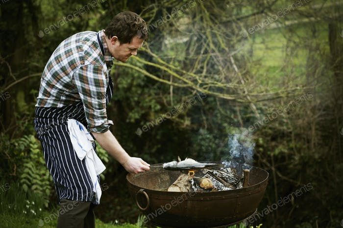 Chef standing in a garden, grilling a fish on a barbecue.