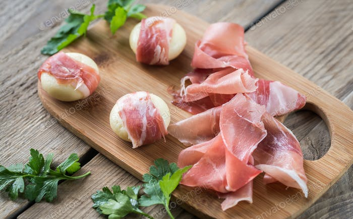 Mini cheese and prosciutto wraps on the wooden board