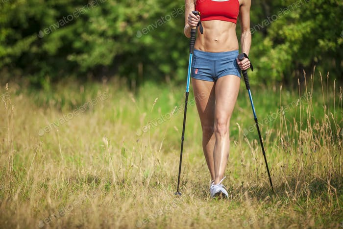 Fit young woman hiking with nordic walking poles in summertime