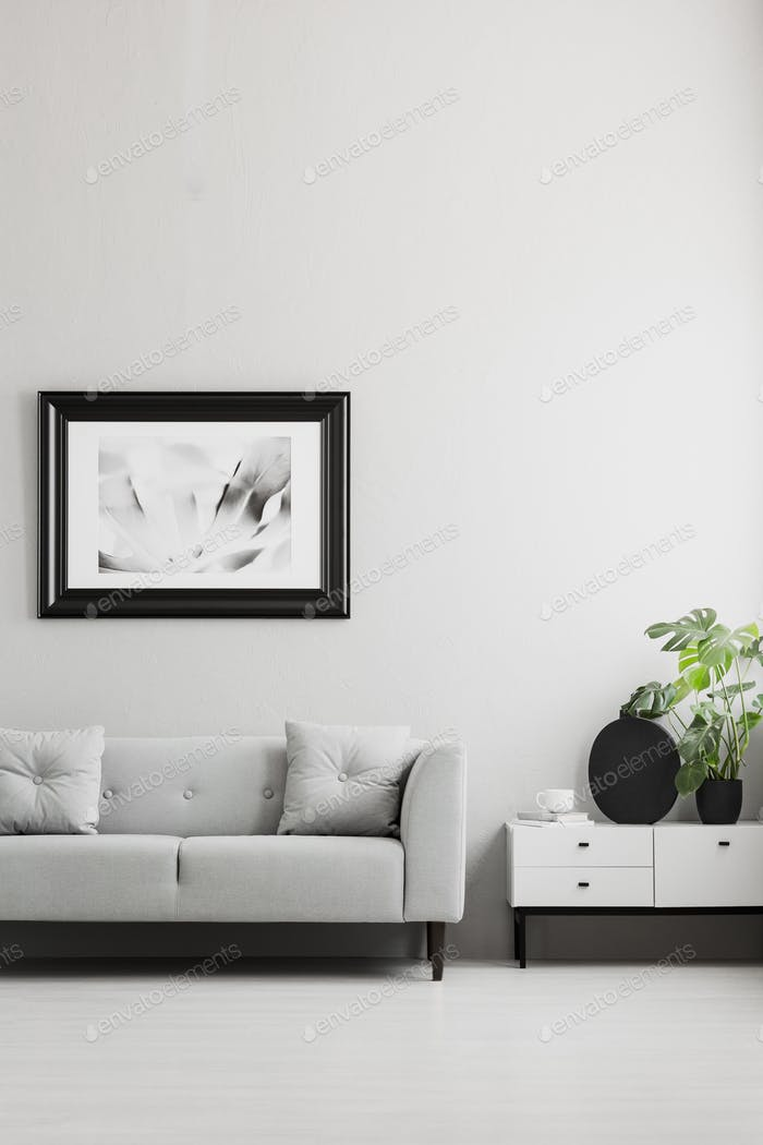 Photo in a black, thick frame on a gray wall, white sideboard an