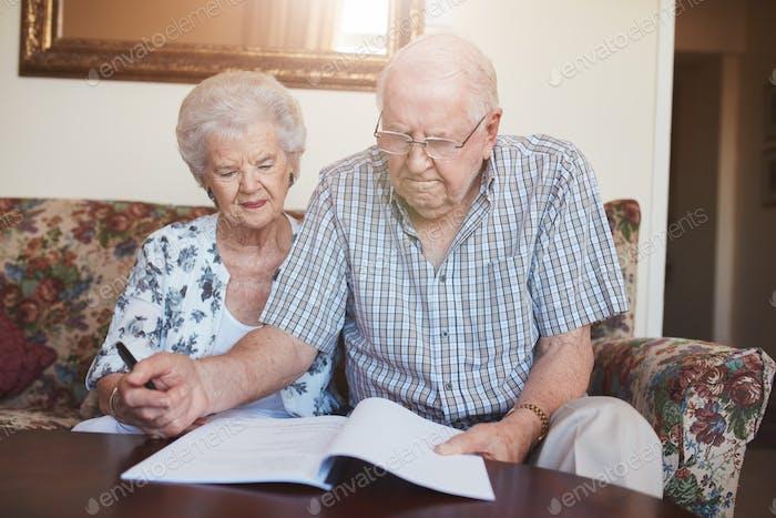 Pensionierte Paar Blick über Dokumente zu Hause