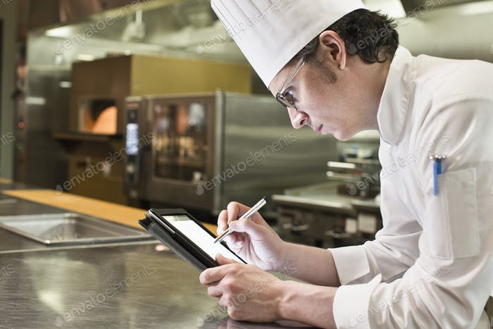 A caucasian male chef working on a notebook computer in a commercial kitchen.