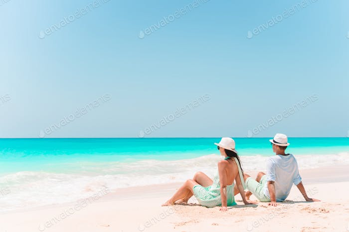 Young couple walking on tropical beach with white sand and turquoise ocean water