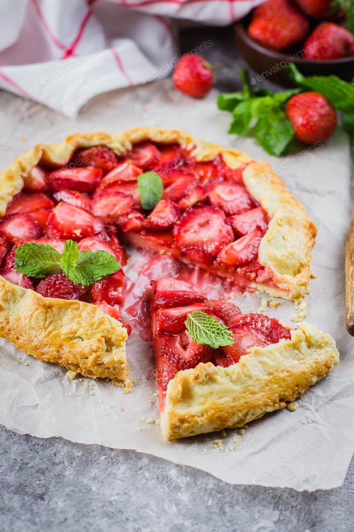 Galette with strawberry on the gray concrete stone background. Vegetarian healthy berry galette