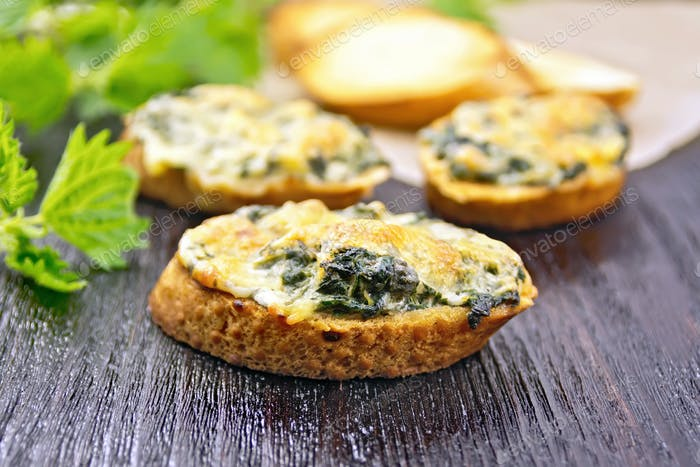 Sandwich of nettle and cheese on dark board