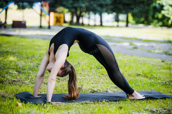 Fit young beautiful woman wearing black sporty leggings working out outdoors in park on summer day