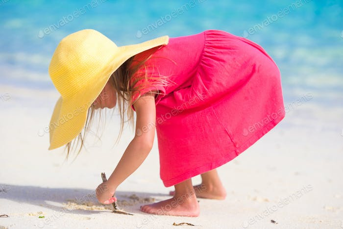 Adorable little girl in hat at beach during summer vacation