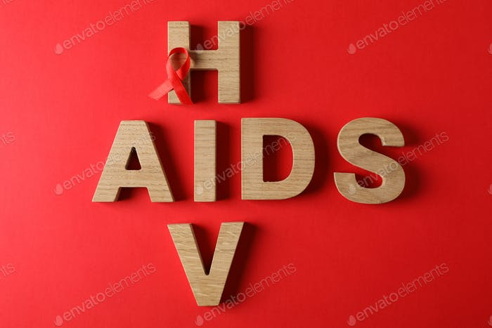 Awareness ribbon and words AIDS and HIV on red background, space for text