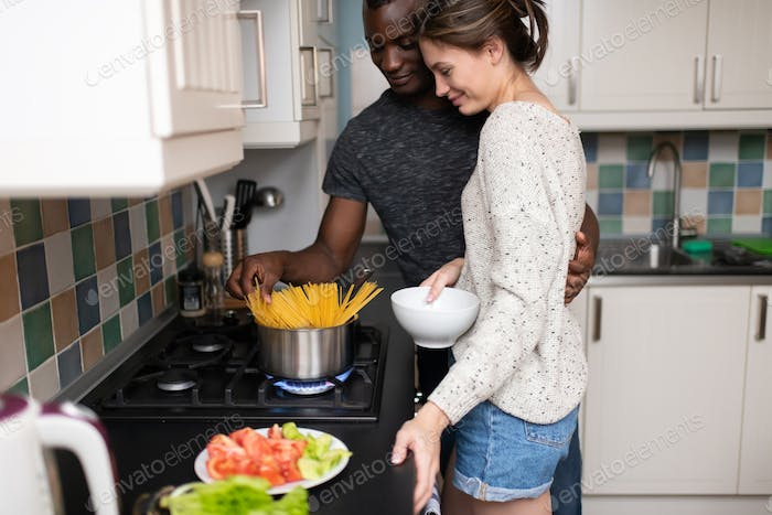 Happy multiracial couple cooking dinner together