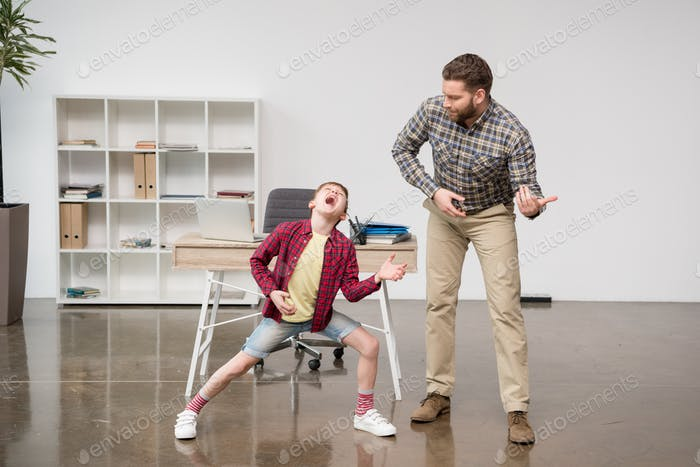 Businessman freelancer playing on imaginary guitar with his son at home office