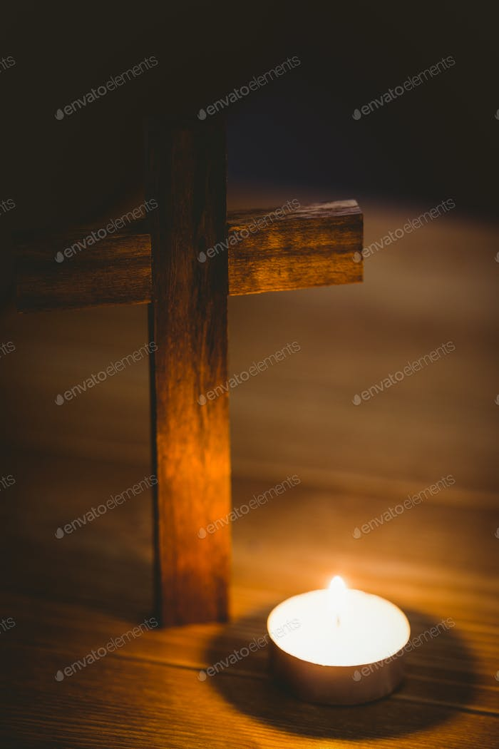 Candle and wooden cross on wooden table