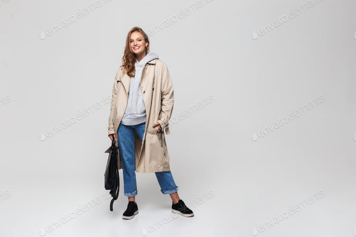 Young smiling woman in trench coat and jeans holding black backpack happily looking in camera