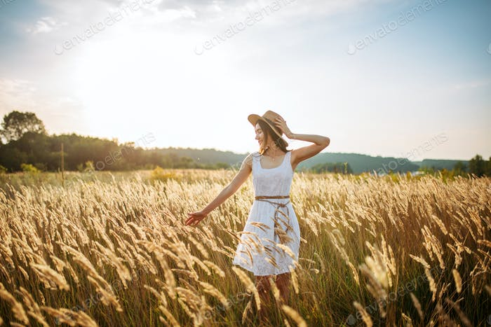 Cute woman harvests wheat in the field