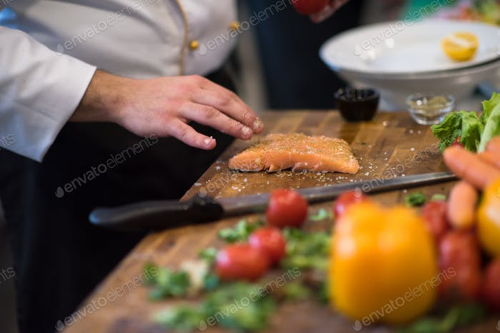 Chef hands preparing marinated Salmon fish