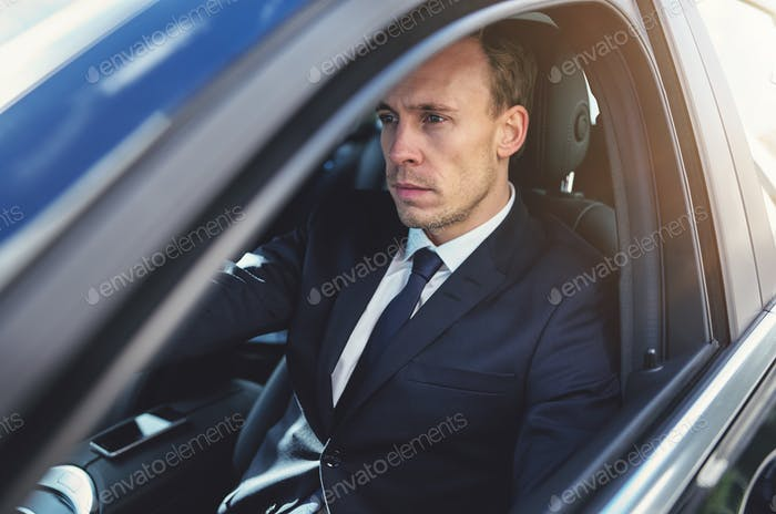 Serious businessman driving his black stylish car