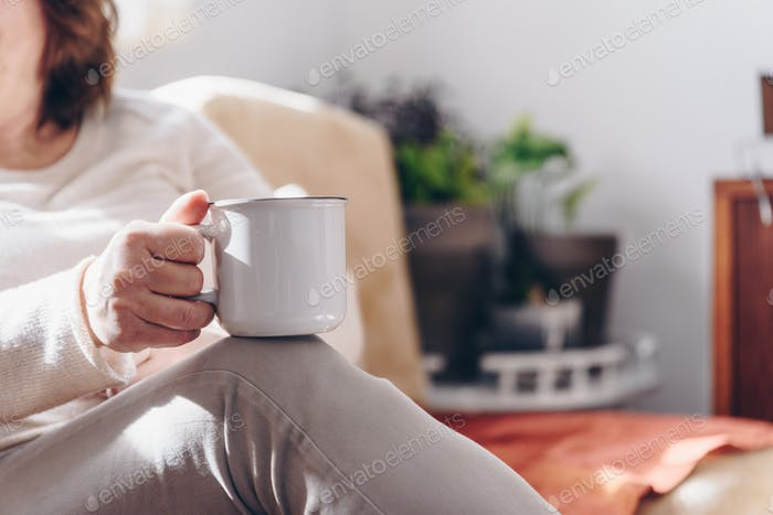 Close up of elderly woman hands while holding a cup of coffee