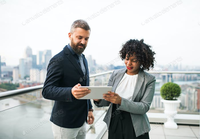 A portrait of two businesspeople with tablet standing against London view panorama.