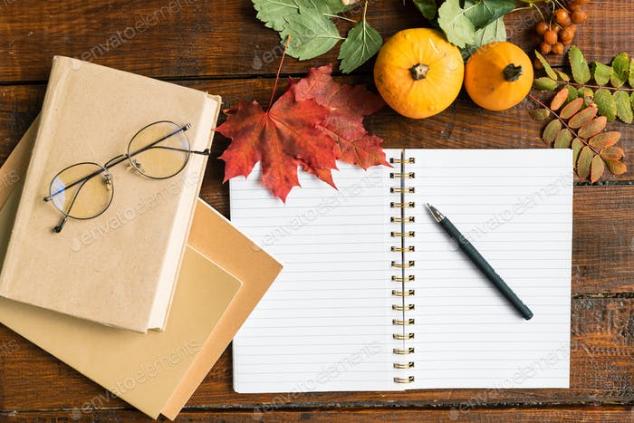 Open copybook with pen, books with eyeglasses, pumpkins and autumn leaves