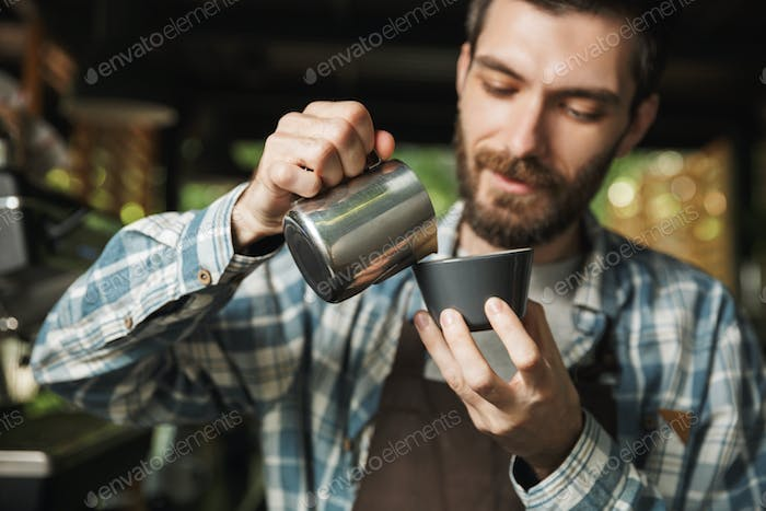 Image of unshaved barista man making coffee while working in caf