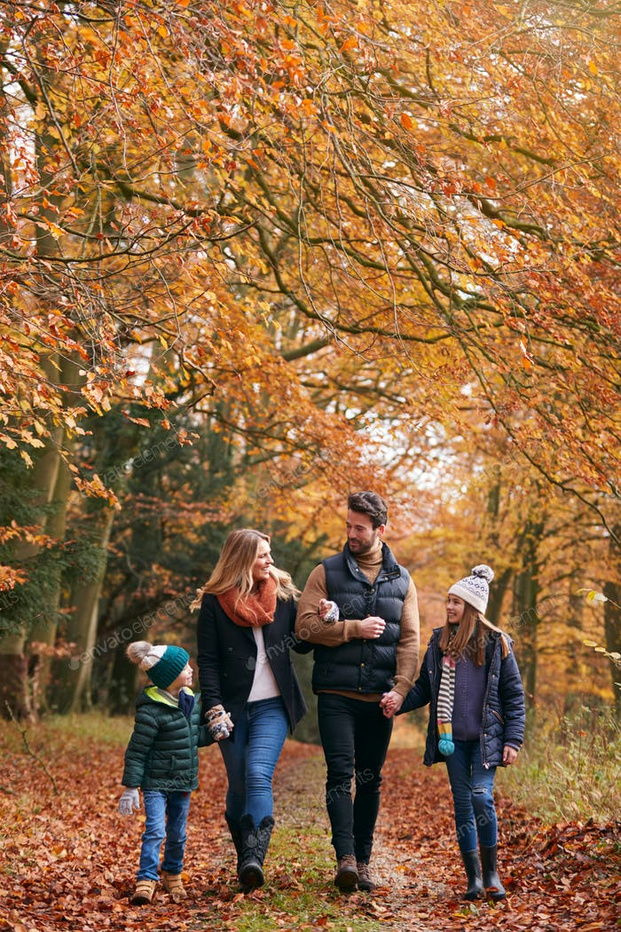 Family Walking Arm In Arm Along Autumn Woodland Path Together
