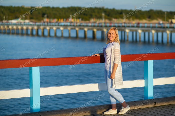 a girl in pants and a jacket stands on a pier near the Baltic Sea.Palanga