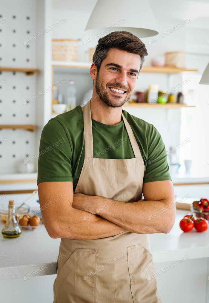 Cheerful young man preparing healthy food in the kitchen