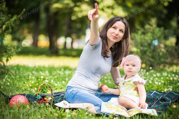 Mother sitting on grass with her small baby daughter and eating fruits