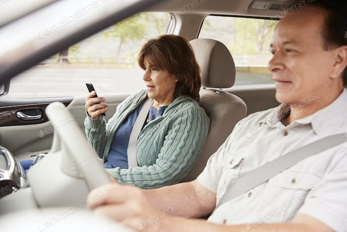 Woman passenger using GPS on smartphone during car journey