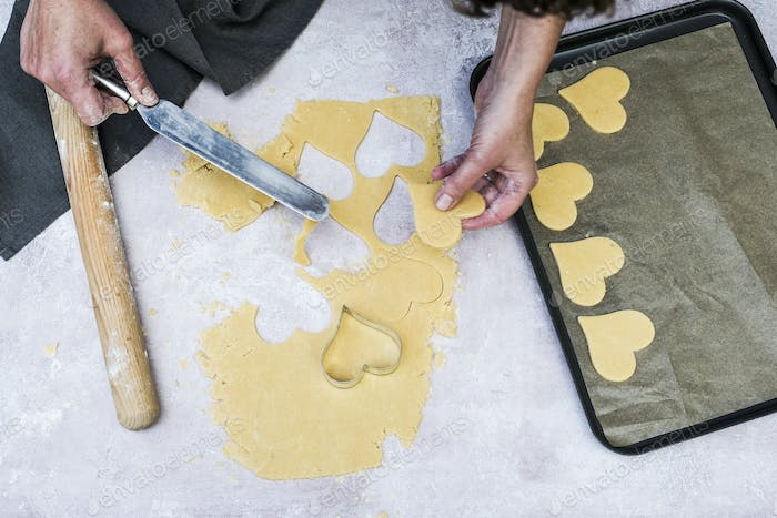 High angle close up of person using palette knife to move heart-shaped cookies onto a baking tray.