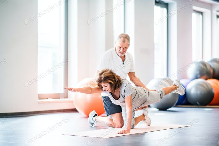 Senior physiotherapist working with a female patient.