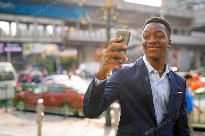 Young happy African businessman taking selfie in the city outdoors