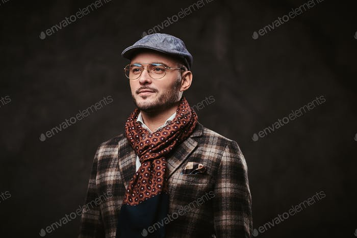 Successful stylish businessman posing in a studio wearing checkered jacket, glasses and scarf
