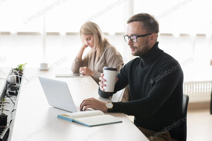 Pensive freelancer using laptop in coworking space