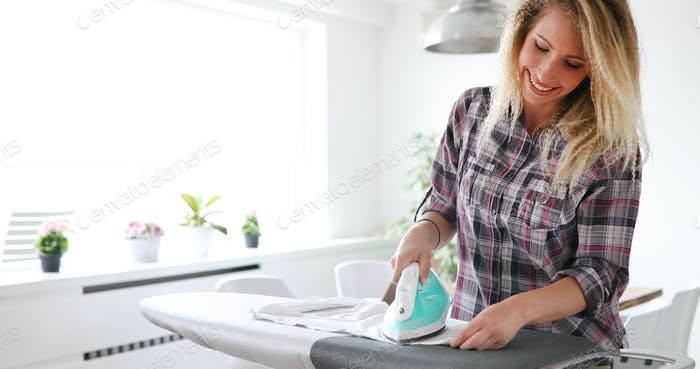 Portrait of young beautiful woman ironing clothes