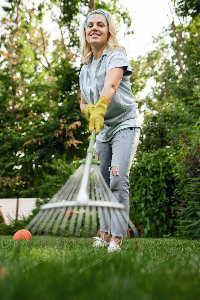 Smiling woman with rake works in the garden