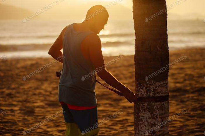 teenage sets up slackline for balancing on the beach