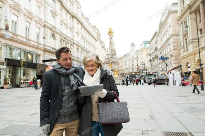 Beautiful senior couple with tablet on a walk in city centre.
