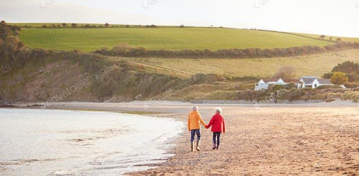 Weitwinkel Rückansicht von Senioren Paar Hand Hand Walking entlang Küste Auf Winter Strand Urlaub