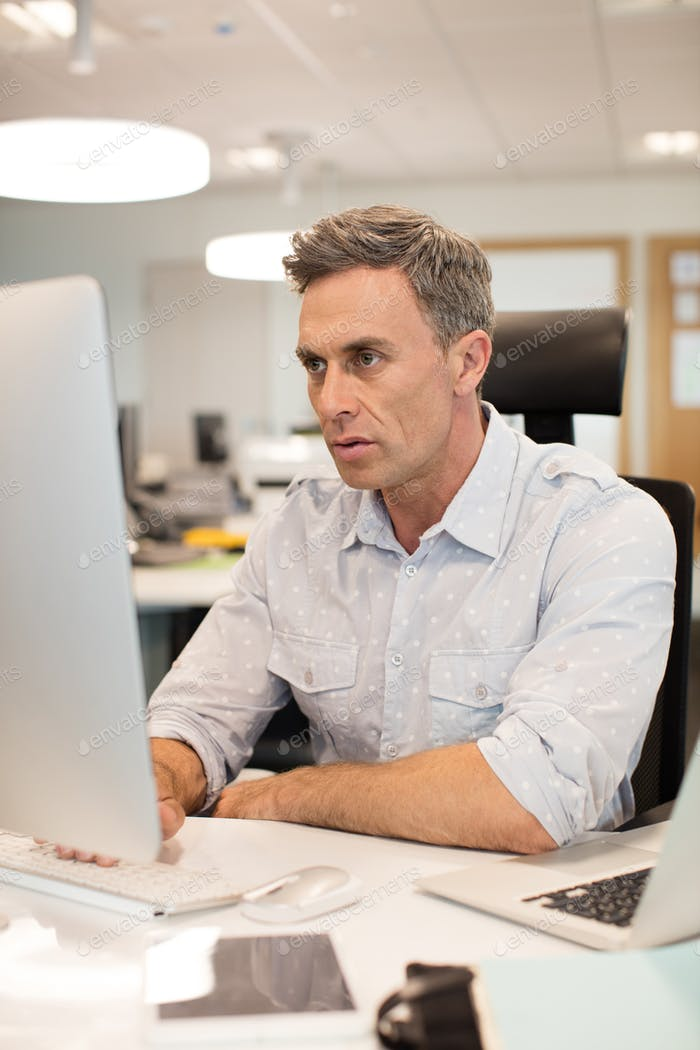 Serious businessman working on computer in office