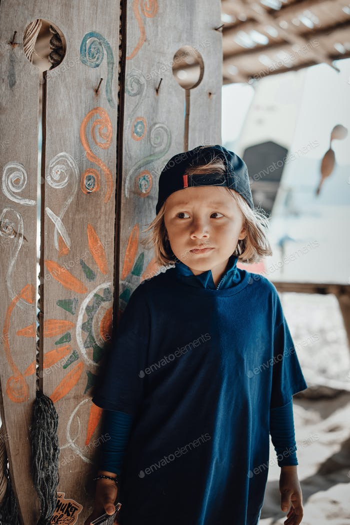 Scary boy looks away near wooden wall with some pictures on seaside