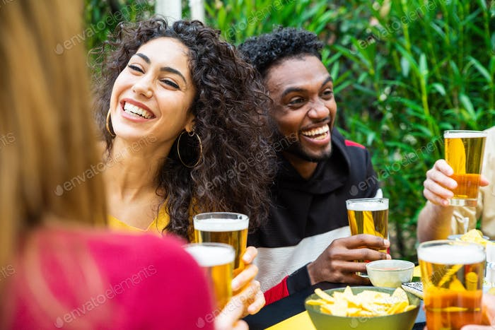 Happy multicultural people drinking beer at restaurant